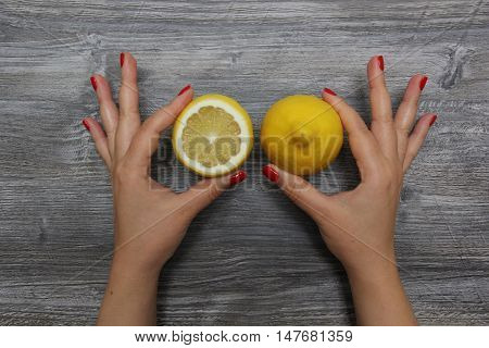 Half a lemon in the left hand and whole lemon in the right hand on the gray wooden textural background