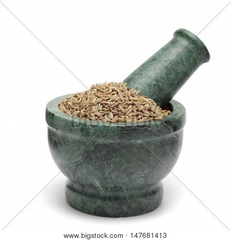 Organic Cumin seed (Cuminum cyminum) on marble pestle. Isolated on white background.