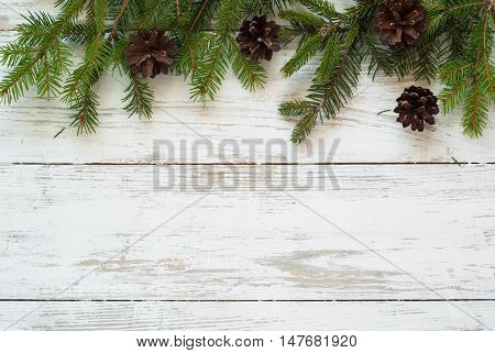 Christmas tree branch with pinecones on white wooden table.