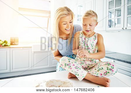 Mother working with child to prepare bread dough for baking in bright indoor kitchen