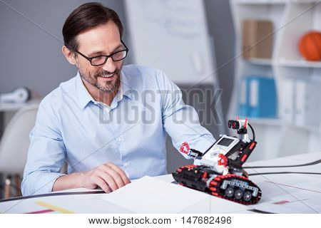 Happy as a kid. White man in glasses trying new electronic device.