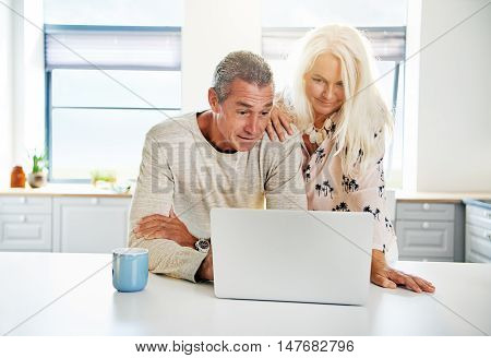 Kitchen scene with calm middle aged couple looking at computer together. Includes copy space in windows and on coffee cup.