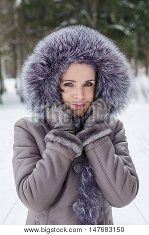 Beautiful woman in winter jacket with fur hood having fun making a funny face c puffed-out cheeks