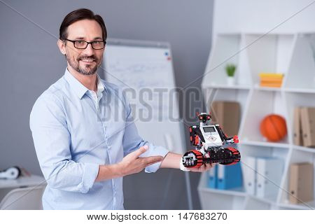 Proud. White male with a beard showing his new electronic device.