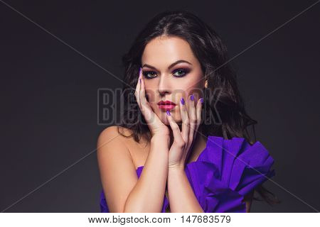 Beautiful brunette young woman with dark smoky eyes make-up in paper dress. Beauty shot over dark background. Copy space.