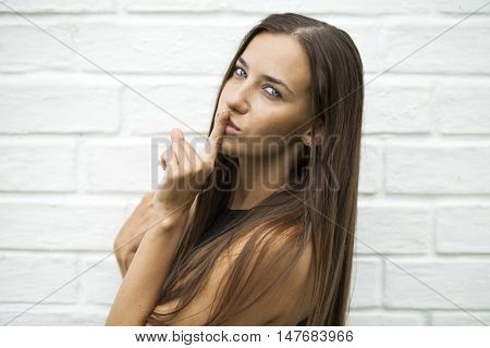 Young beautiful brunette woman has put forefinger to lips as sign of silence, against white wall