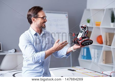 Wonderful invention Middle-aged professor admiring his newly created droid