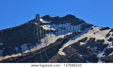 Summit station of a cable car. Suspension bridge connecting two mountain peaks. Sex Rouge Glacier des Diablerets. Travel destination in the Swiss Alps.