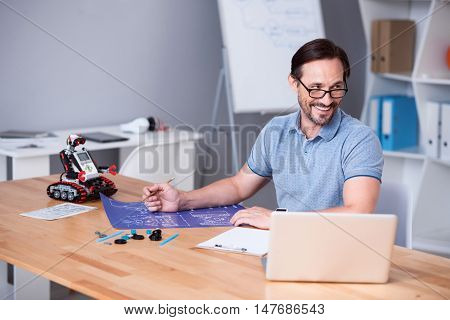 Involved in project. Cheerful professional engineer working on the project and sitting at the table while expressing gladness