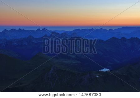 Lake Arnensee and surrounding mountains on a summer morning. View from Sex Rouge Glacier des Diablerets. Swiss Alps.