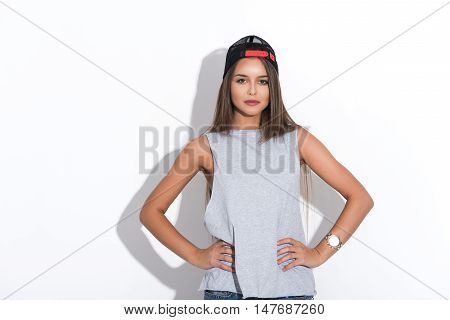 Confident hipster girl is standing with arms akimbo. She is wearing cap. Isolated
