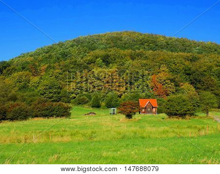Meadow and colorful deciduous forest during autumn, cottage under this forest
