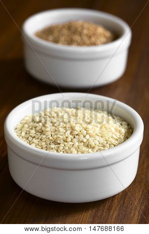White and roasted sesame seeds in small bowls photographed with natural light (Selective Focus Focus one third into the white seeds)