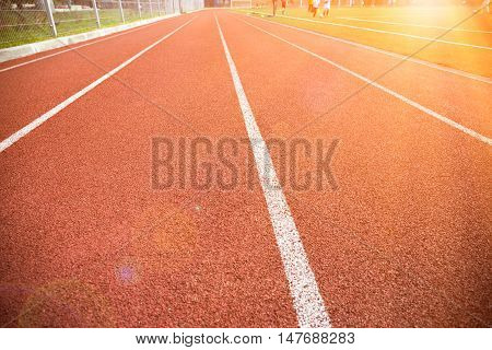 Lanes on a running track with sunlight