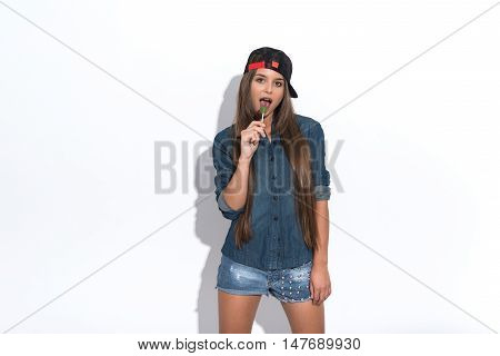 Cool young woman is licking sweet candy with pleasure. She is standing and posing. Isolated and copy space in left side