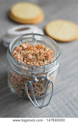 Roasted and smoked salmon fish, soft cheese and egg pate in glass jar, selective focus
