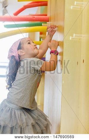 child girl climbing a wall in indoor playarea