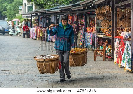 Yangshuo China - October 21 2013: Chinese woman carries baskets of produce and fruit to sell in the local market in Yangshuo China.
