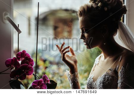 young sexy wedding woman or girl bride silhouette with flowers in stylish blonde hair and on pretty face in wedding dress near curtain and bouquet on window