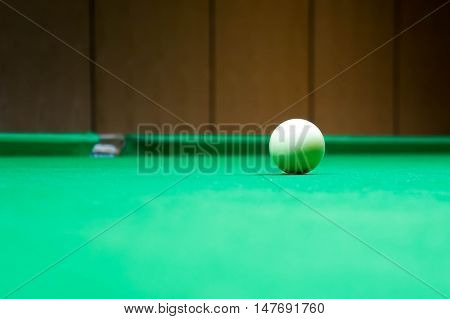 Billiard cue ball solid white color on green table background.