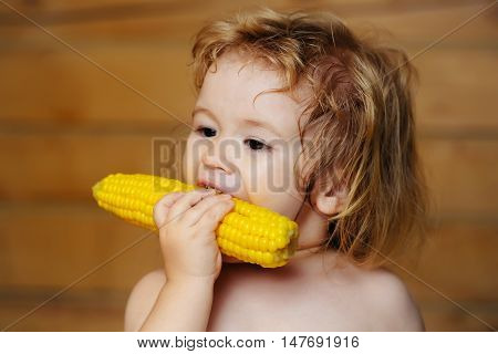 Small boy child with long blonde hair eating yellow corn or maize with bare chest and funny face on wooden or wood background