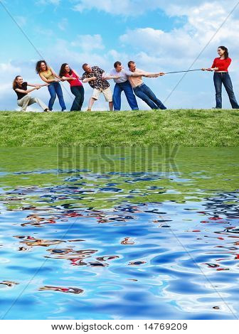 Group of happy people pulling the rope with reflection
