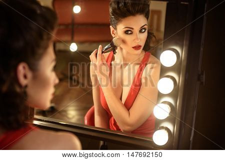 Young woman is doing make-up backstage. She is sitting and looking at mirror with confidence. Model is touching brush to cheek