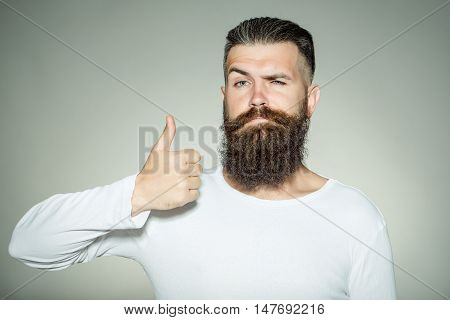 handsome young man with long beard and moustache on face with super gesture showing thumb up on grey background in studio