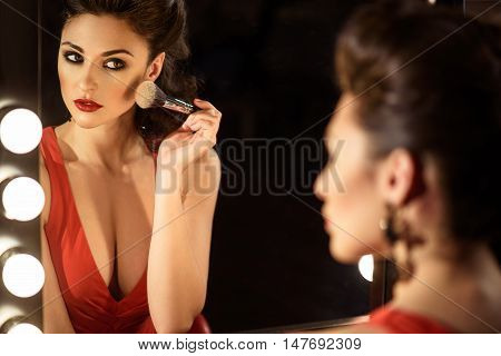 Attractive young woman is applying powder on her face. She is looking at mirror with satisfaction