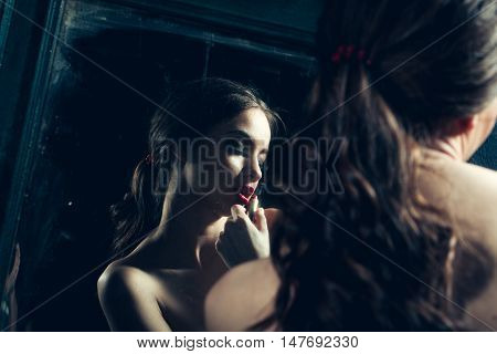Sensual young lady with bare chest and curly hair near old dirty vintage mirror with lipstick