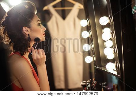 Professional female model is preparing her appearance in dressing room. She is applying powder on face with concentration. Girl is sitting in front of mirror