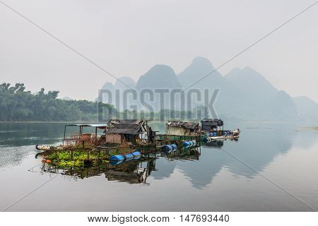 Yangshuo China - October 21 2013: Houses and bamboo raft on the Li river floating island in the overcast nasty day in rural Yangshuo China.
