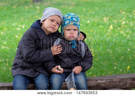 The elder brother is six years old comforting his younger brother three years