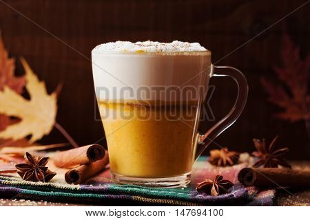 Pumpkin spiced latte or coffee in a glass on a wooden vintage table. Autumn or winter hot drink.