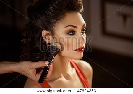 Close up of beautician hand applying powder on female face. Young woman is sitting and looking forward with confidence