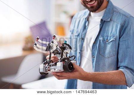Smart technologies in use. Positive delighted smiling man holding robot and expressing positivity while standing in the office
