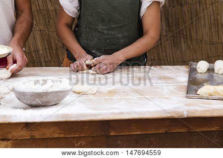 woman hands kneading bread on a wooden table