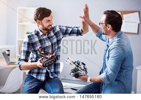 On the edge of emotions. Cheerful delighted colleagues sitting on the table and holding robots while giving high five.