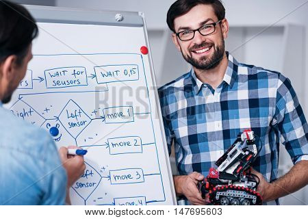 Involved in cooperation. Positive man smiling and holding robot while standing near board with his colleague in the office