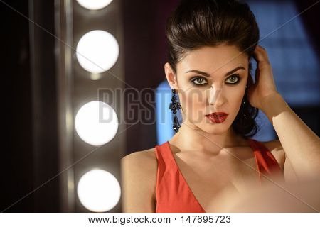 Passionate young woman is looking at her reflection in mirror with confidence. She is sitting and touching her hair backstage