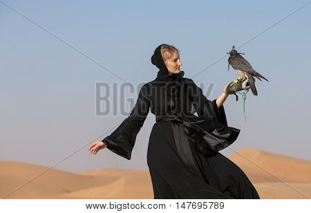 emirati woman, wearing a traditional dress (abaya) with a falcon in desert