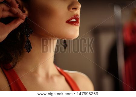 Close up of elegant young woman wearing earring on her ear