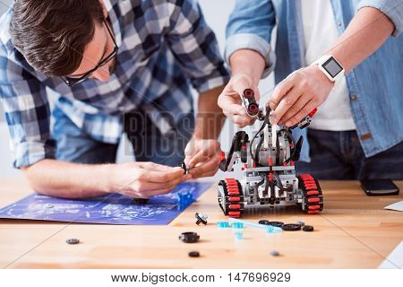 Involved in process. Pleasant concentrated colleagues standing near table and constructing robot while working in the office