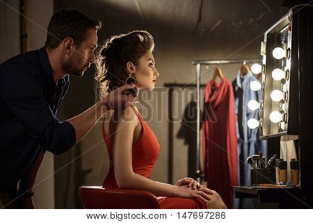Professional male beautician is applying powder on female skin with concentration. Woman is sitting on chair backstage