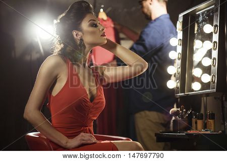 Confident young woman is posing in front of the mirror. She is sitting on chair backstage. Man is standing and holding clothing on background
