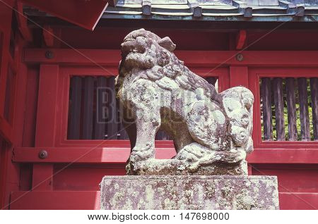 ancient stone sculpture of lion guard with red fence of Japanese temple behind