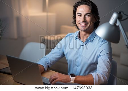Work productively. Satisfied young handsome man smiling and using laptop while sitting at the table.
