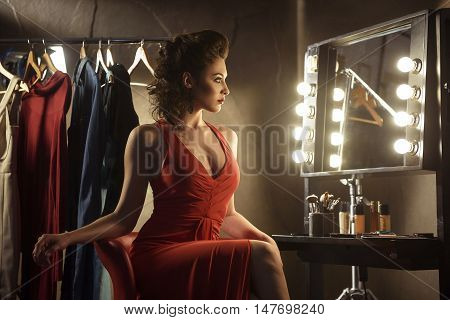 Beautiful female model is sitting and relaxing backstage. She is looking at mirror with confidence