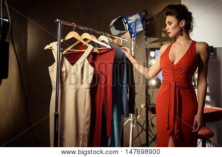 Attractive young woman is choosing fashionable clothing backstage. She is standing and looking at dress with desire