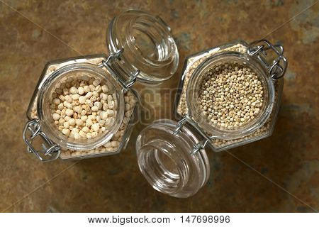 Popped quinoa cereal and raw white quinoa grains (lat. Chenopodium quinoa) in glass jars photographed overhead on slate with natural light (Selective Focus Focus on the top of the popped quinoa cereal and the quinoa)